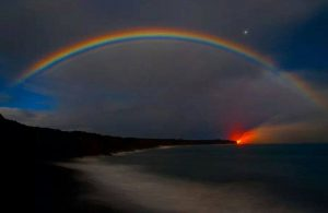 Night-time colorful rainbow over the beach with the sun setting